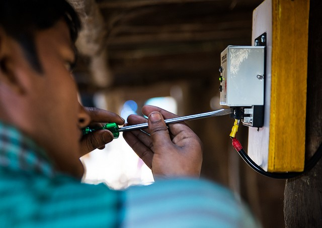 Installing solar lighting. Photo by Jarnail Singh/The Climate Group