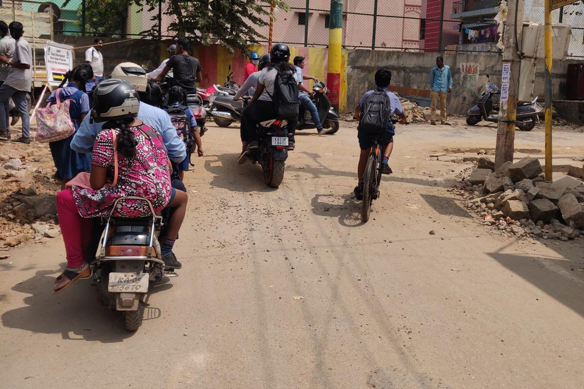 School children walking and cycling on a street without footpaths or bicycle lanes in Bengaluru.